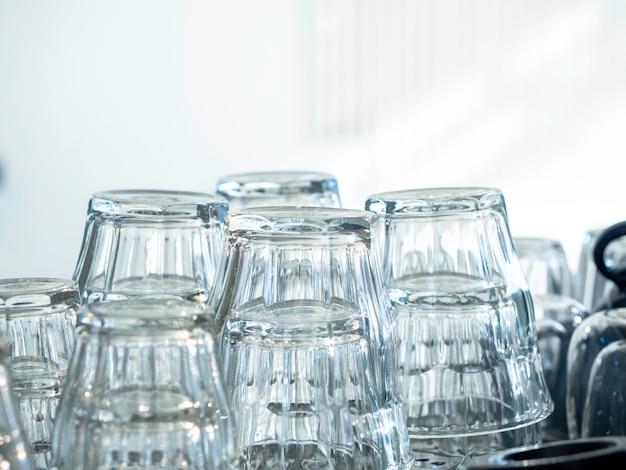 Chiudere a testa in giù bicchieri di acqua potabile vuoti. pile di vetro vuoto pulito e secco sul fondo bianco della parete in caffè.