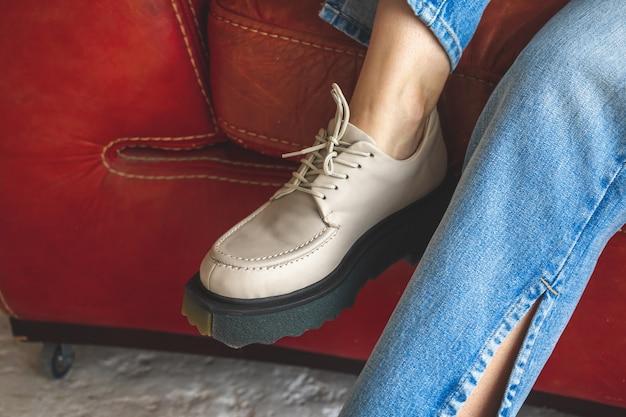 Primo piano di scarpe da ginnastica urbane su una ragazza adolescente seduta su una vecchia poltrona in pelle in stile retrò e vintage