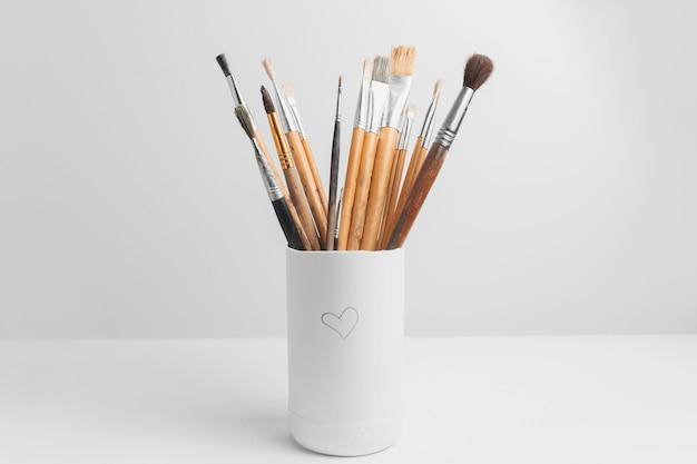 Primo piano dei pennelli per pittura usati su sfondo bianco per studio.