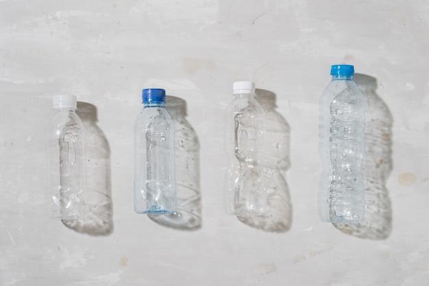 Primo piano di bottiglie di plastica usate su sfondo bianco