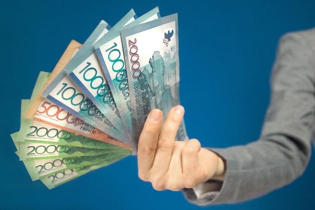 Close-up di varie denominazioni di banconote tenge denaro kazako in mano su sfondo blu. messa a fuoco selettiva.