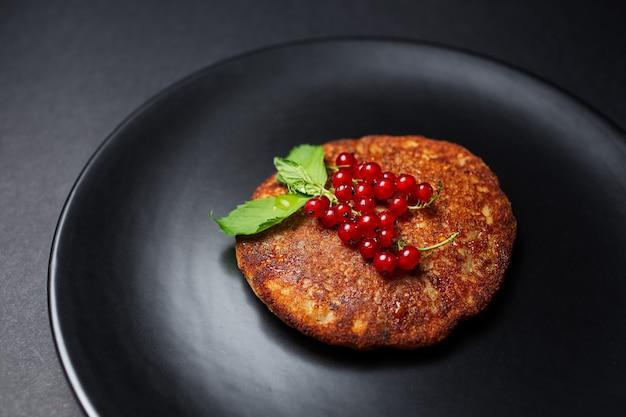 Primo piano del pancake fatto in casa vegano con ribes rosso sulla banda nera.