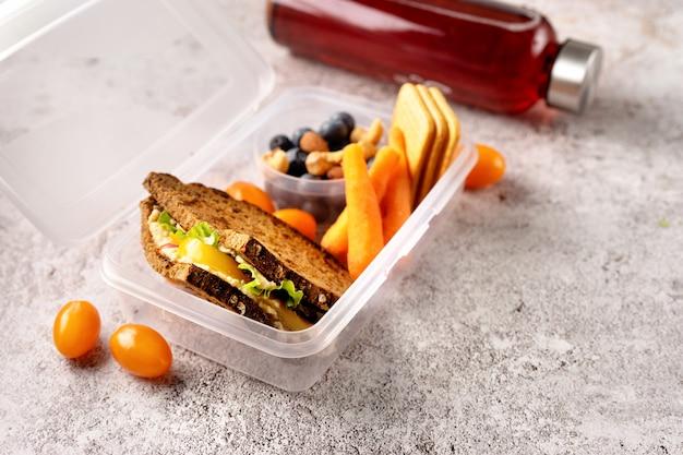 Chiuda su della scatola di pranzo della scuola vegana con il panino, le carote e le bacche su fondo concreto grigio