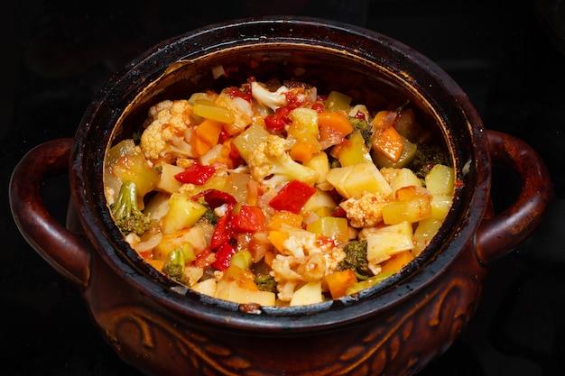 Close-up di uno stufato di verdure in una pentola. varie verdure tritate finemente stufate in una casseruola. cibo nazionale. concetto di cibo sano. concetto di cibo vegetariano