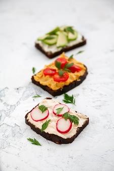 Close-up vegetariano pane di segale toast con ricotta, hummus, avocado, ravanello e pomodoro su un bianco