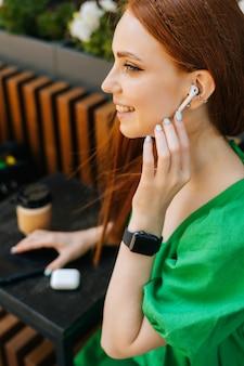 Primo piano verticale di allegra giovane donna che ascolta musica utilizzando auricolari wireless e telefono cellulare seduto al tavolo, nella terrazza del caffè all'aperto in una giornata estiva, sfondo sfocato, messa a fuoco selettiva