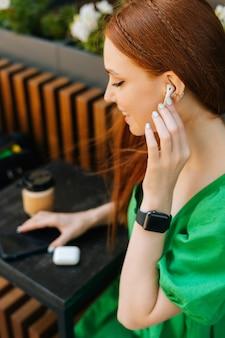 Primo piano verticale di una giovane donna sorridente che ascolta musica utilizzando auricolari wireless