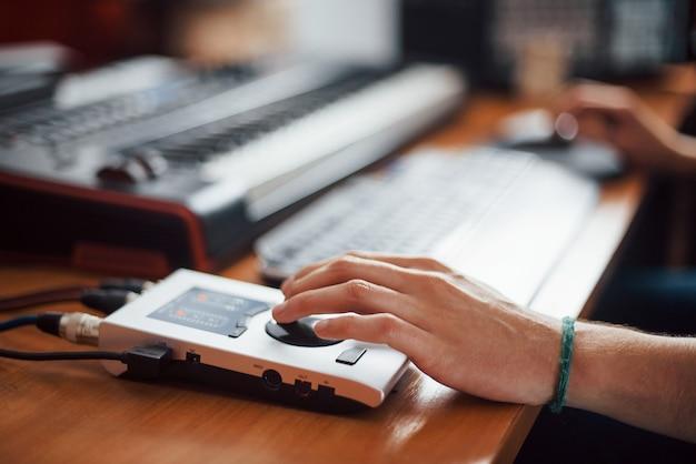 Vista ravvicinata della mano sull'interfaccia. ingegnere del suono che lavora e mixa musica all'interno dello studio.