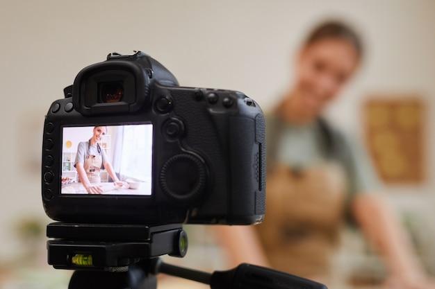 Primo piano della videocamera con la donna sullo schermo blogger alimentare che fa un contenuto