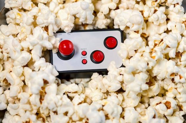 Primo piano del controller per videogiochi e popcorn. pomeriggio di videogiochi e popcorn, serata tra amici.