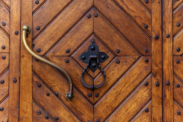 Una vista ravvicinata di un'antica porta di legno con una serratura arrugginita. una bella struttura in legno.