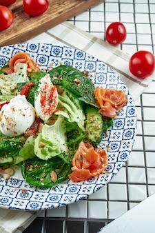 Chiuda sulla vista su insalata appetitosa con salmone, spinaci, uovo in camicia e ricotta nel bellissimo piatto in ceramica blu sulla superficie bianca. cibo gustoso. disteso