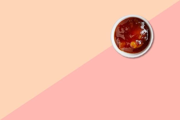 Vista ravvicinata porridge di tapioca asiatico con ceramica bianca isolata su sfondo rosa.