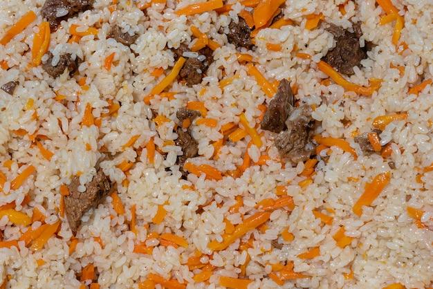 Vista ravvicinata dello sfondo di cibo gustoso asiatico. piatto culinario orientale tradizionale - pilaf. ingredienti: riso con fettine di carne, grasso e verdure carota, aglio, spezie - ricetta popolare.