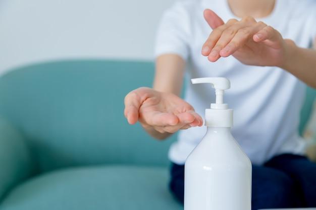 Vista ravvicinata della donna asiatica che utilizza il disinfettante gel alcolico lavarsi le mani per proteggere dal coronavirus. concetto di igiene e assistenza sanitaria.