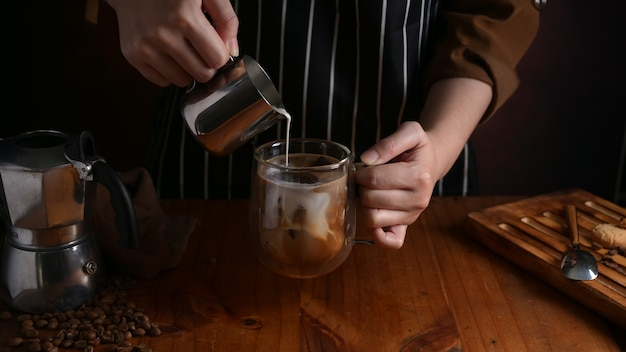 Vista ravvicinata del barista versando il latte in una tazza di caffè sul bancone in legno bar nella caffetteria