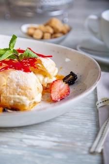Primo piano vista del bellissimo dessert dolce elegante, napoleone, servito sul piatto. splendida decorazione, piatto del ristorante, pronto da mangiare. ora del tè, atmosfera accogliente.