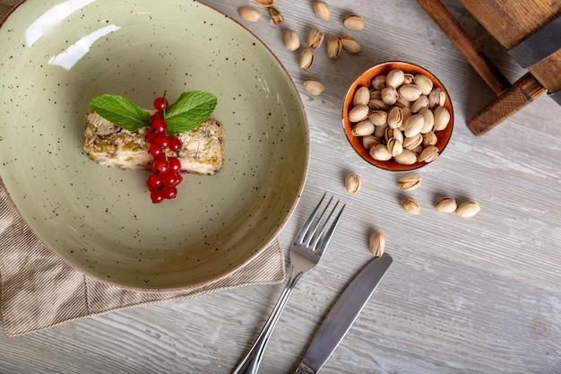 Chiuda sulla vista di bello dessert dolce elegante, roulette del pistacchio, servita sul piatto