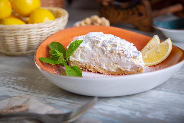 Chiuda sulla vista di bello dessert dolce elegante servito, torta del limone, sul piatto
