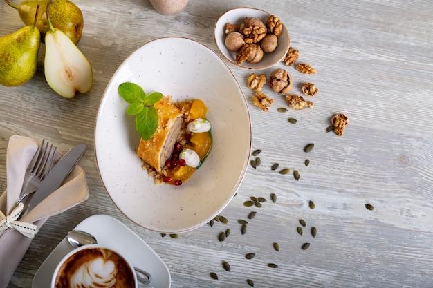 Chiuda sulla vista di bello dessert dolce elegante servito, rotolo della noce, sul piatto. splendida decorazione, piatto del ristorante, pronto da mangiare. ora del tè, atmosfera accogliente.