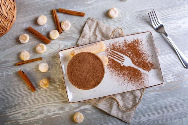 Chiuda sulla vista di bello dessert dolce elegante, tiramisù, servito sul piatto