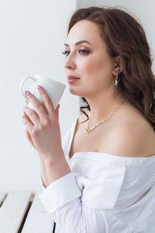 Vista ravvicinata di belle mani femminili che tengono grande tazza bianca di caffè cappuccino.