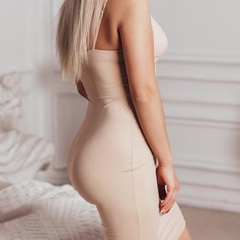 Vista ravvicinata del corpo di bella donna in abito sexy beige in camera da letto