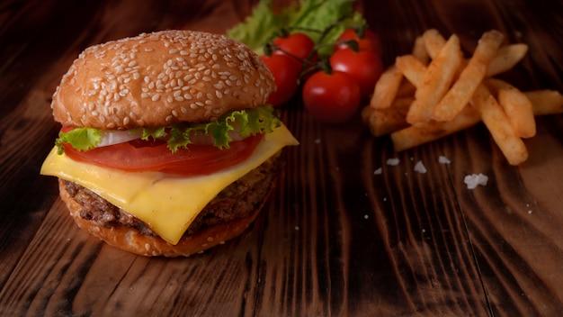 Chiuda sulla vista dell'hamburger di manzo con le patate fritte, gli ingredienti e lo spazio della copia