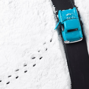 Vista ravvicinata della macchinina blu con la neve