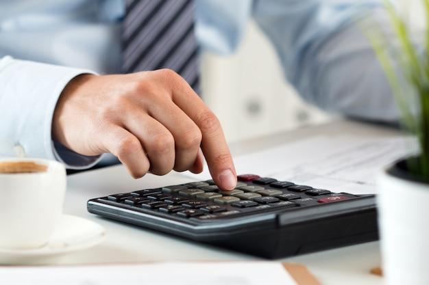 Vista ravvicinata delle mani del contabile o dell'ispettore finanziario che fanno rapporto, calcolo o controllo dell'equilibrio