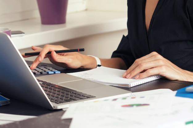 Vista ravvicinata delle mani di contabile o ispettore finanziario che fanno rapporto, calcolo o controllo dell'equilibrio