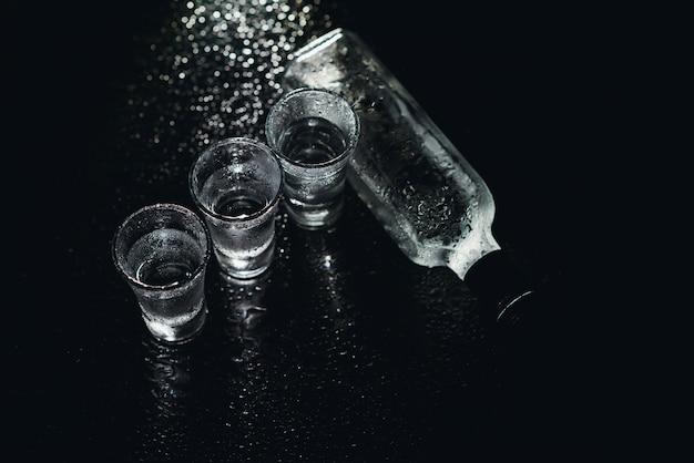 Vista ravvicinata di bottiglia e bicchieri di vodka in piedi isolato su nero