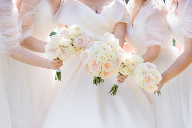 Vista ravvicinata della sposa e quattro damigelle che tengono bellissimi mazzi di fiori alla moda con rose fresche