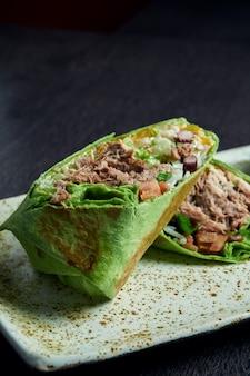 Chiuda sulla vista sul burrito con manzo, riso, pomodori, mais e peperone in pita verde su un piatto marrone con salsa di pomodoro e guacamole. rotolo vegetariano shawarma