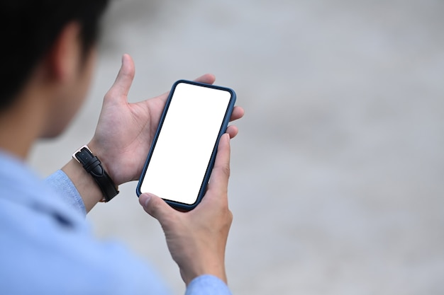 Vista ravvicinata dell'uomo d'affari utilizzando il telefono cellulare con schermo vuoto all'aperto.