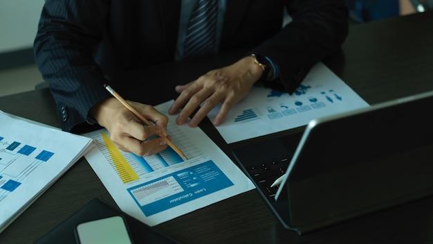 Vista ravvicinata di imprenditore analizzando sui documenti aziendali sulla scrivania in ufficio