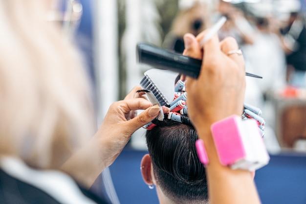 Vista ravvicinata di un parrucchiere caucasico che fissa i capelli di un cliente con rulli per tingerli