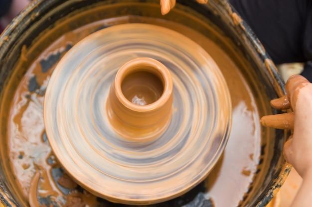 Una vista ravvicinata sul processo di produzione della ceramica sul tornio da vasaio con bambini artigianato in argilla con bambino