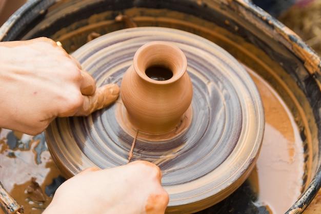 Una vista ravvicinata sul processo di produzione della ceramica sul tornio da vasaio con bambini artigianato in argilla con bambini