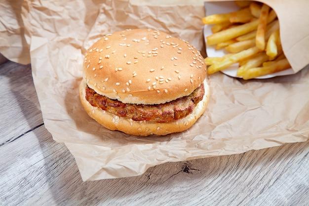 Chiuda sulla vista sull'hamburger di pollo con le patate fritte sulla carta marrone del mestiere. fast food tradizionale. burger fresco gustoso con braciola di pollo. copia spazio per il design. cibo malsano. grasso