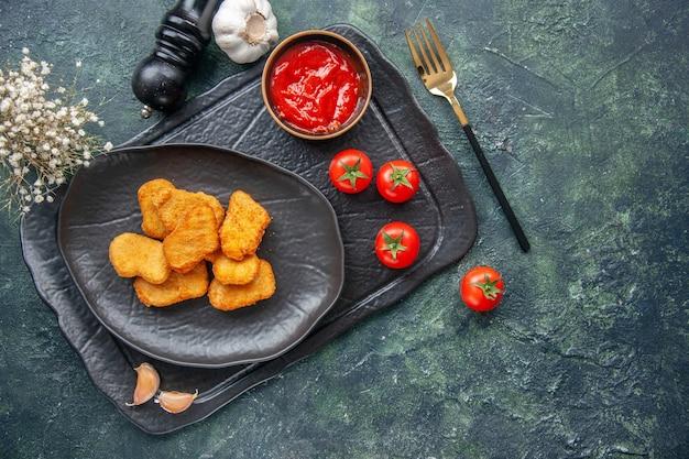 Vista ravvicinata di pepite di pollo su un piatto nero ed elegante ketchup a forchetta su vassoio di colore scuro pomodori a fiore bianco con aglio a stelo