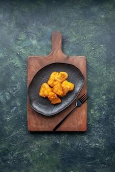 Vista ravvicinata delle pepite di pollo su tagliere di legno su superficie scura con spazio libero