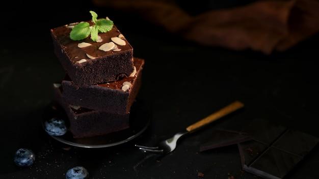 Chiuda sulla vista dei brownies al cioccolato sulla banda nera con la foglia di menta sulla cima