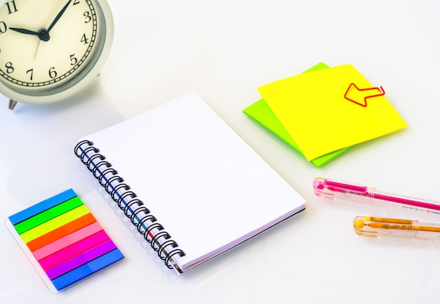Primo piano vista di appunti con carta bianca, gomma gialla, matite colorate, adesivi, temperamatite, evidenziatori, punti metallici.