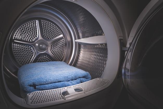 Vista ravvicinata di un'asciugatrice con asciugamani blu all'interno e una porta aperta in una stanza buia