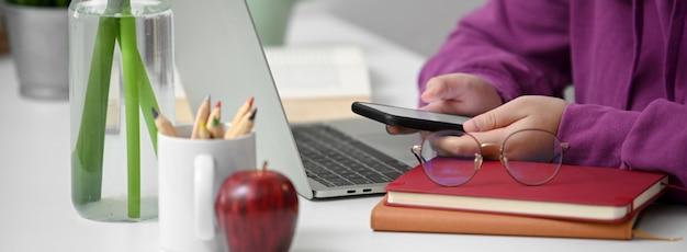 Primo piano vista di studente universitario utilizzando smartphone mock-up per contattare i suoi amici