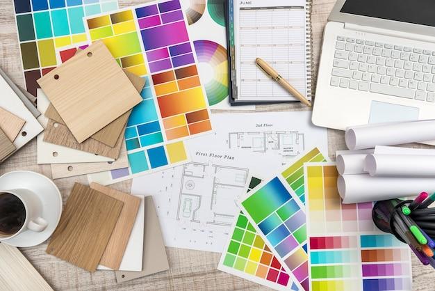Vista ravvicinata del campione di tavolozza dei colori e piani di costruzione di una casa sulla scrivania in ufficio con laptop e tazza di caffè per la pausa.