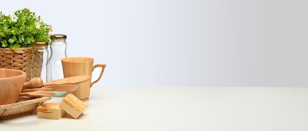 Vista ravvicinata della scena creativa con stoviglie in legno, vaso per piante e copia spazio sul tavolo bianco, concetto di rifiuti zero