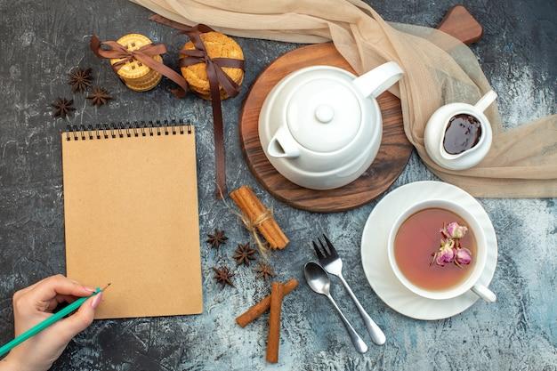 Vista ravvicinata di una tazza di tè nero e bollitore su biscotti per notebook su tavola di legno su sfondo di ghiaccio