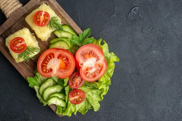 Vista ravvicinata di pomodori e cetrioli freschi tagliati su tavola di legno su superficie nera